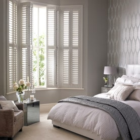 Bay window shutters in a bedroom