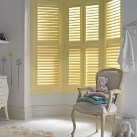 Yellow bay window shutters in a nursery