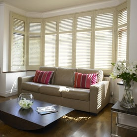 Beige bay window shutters in large living room