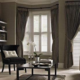 White bay window shutters in a living room