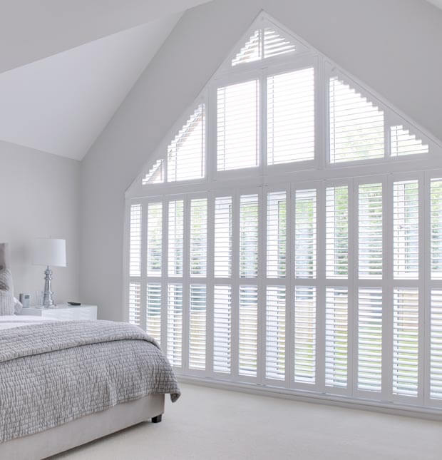 Shaped white shutters on gable wall in bedroom