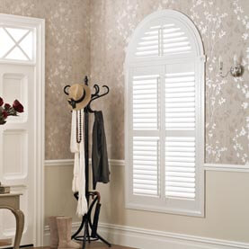 Curved white shutters in hallway