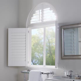 Curved white shutters in bathroom