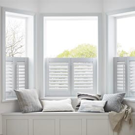 White café style shutters next to window seat