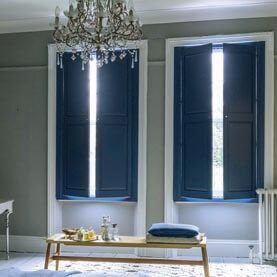 Navy blue solid shutters covering two windows
