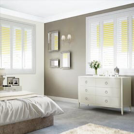 White blackout shutters coupled with a yellow Duette blind