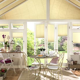 Yellow blinds dressing bi-fold doors in conservatory