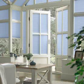 Light blue blinds on French doors in orangery
