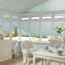 Light blue Pleated blinds across conservatory windows and roof