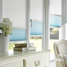 White and light blue twin shade blinds on tall windows