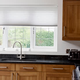 White Duette blinds showing water resistant qualities above kitchen sink