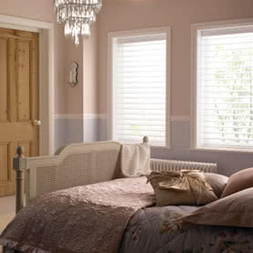 Two windows with open blinds in bedroom