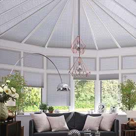 Grey shaped roof blinds in large conservatory
