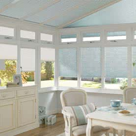 Light blue pleated blinds on conservatory roof and windows