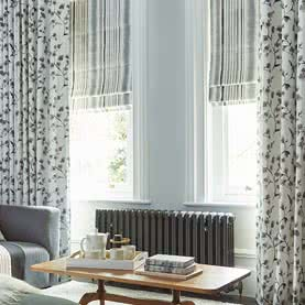 Floral curtains with Roman blinds in a living room