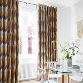 Patterned Eyelet curtains hanging in a living room