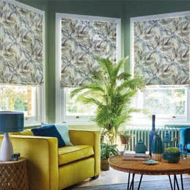 Three rectangular windows covered by Roman blinds