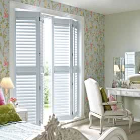 Tracked French door shutters in bedroom