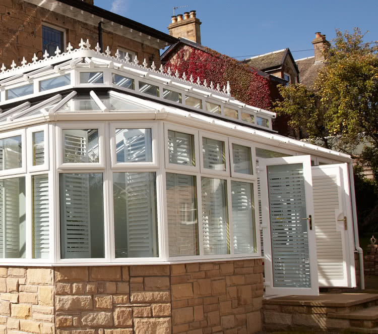 Vinyl French door shutters on front of conservatory