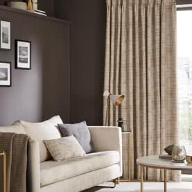 Neutral Pinch Pleat curtains next to living room sofa