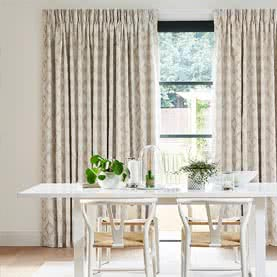 Neutral pinch pleat curtains next to dining room table